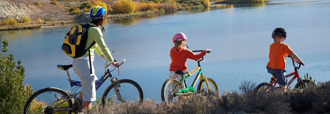 Family cycling along a river trail, New Zealand