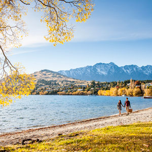 Couple walking along the lakeshore, Queenstown, New Zealand
